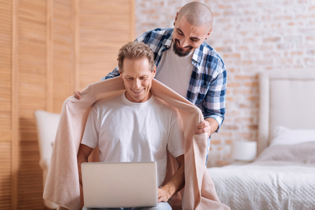 Expressing care towards the partner. Happy positive non-traditional couple standing in the bedroom and expressing love and care while hugging and using the laptop