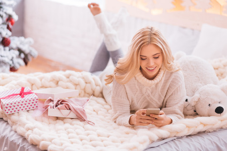 Electronic device. Positive good looking pleasant woman lying on the bed and holding a cell phone while using it