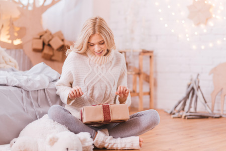 What is inside. Pleasant attractive curious woman holding a Christmas box and opening it while sitting on the floor