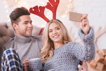 christmas memories: Happy memories. Delighted young blonde woman holding her cell phone and taking a selfie while celebrating Christmas with her boyfriend