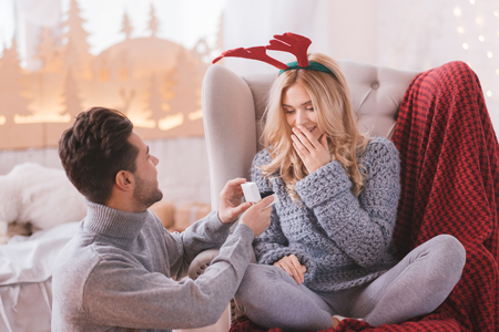fiancee: What a surprise. Surprised astounded happy woman sitting cross legged in the armchair and looking at the engagement ring while getting a marriage proposal