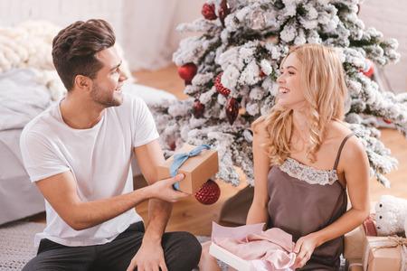 potěšen: Vánoční dárky. Pěkná půvabná příjemná žena, která se dívá na svého přítele a přijímá vánoční dárek, když sedí pod vánočním stromem Reklamní fotografie