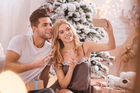 Cute photos. Joyful happy positive couple sitting in front of the Christmas tree and looking into the camera while taking selfies