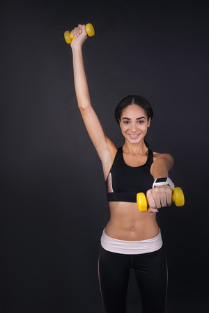 Train with me. Cheerful optimistic sportswoman holding yellow dumbbells in both hands wearing tracksuit standing over black background Stock Photo