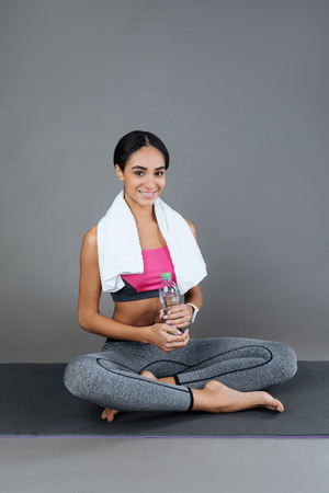 Buy water. Pleasant smiling female holding bottle of water in both hands looking at camera while sitting on the fitness matrass Stock Photo