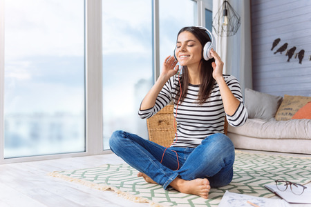 Enjoyable tunes and melodies. Delighted inspired peaceful woman sitting at home and listening the music while expressing happiness