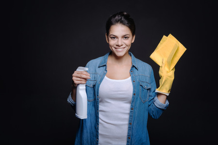 rubber gloves: Ready for cleaning up. Delighted young pleasant woman holding a glass cleaner and a duster while wearing rubber gloves and standing isolated in black background