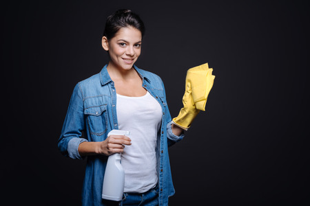 rubber gloves: I enjoy the cleanliness. Delighted smiling young woman holding a glass cleaner and a duster while wearing rubber gloves and standing isolated in black background Stock Photo