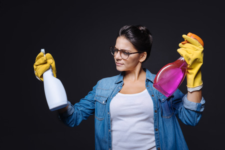 doubtfulness: Which one is better. Puzzled doubtful young woman holding two glass cleaners and wearing rubber gloves while standing against black background and trying to make a decision
