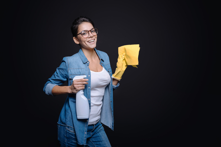 rubber gloves: Cleaning can be funny. Delighted amused young woman holding a duster and wearing rubber gloves while standing against black background and trying to shoot from the glass cleaner Stock Photo