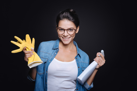 rubber gloves: I like cleanness in everything. Pleasant delighted young woman holding rubber gloves and a glass cleaner while standing isolated in black background and smiling Stock Photo