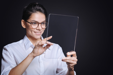involvement: Modern technologies in my hands. Cheerful involved young woman holding the tablet and standing against black background while expressing involvement and testing the tablet