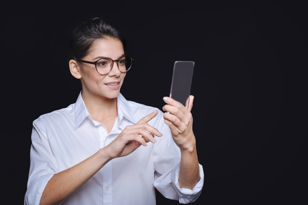 involvement: My new smartphone. Smiling involved young woman holding the phone and standing against black background while expressing involvement and testing the gadget