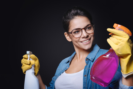 rubber gloves: Time to choose. Doubtful smiling happy woman holding two glass cleaners and wearing rubber gloves while standing against black background and trying to make a decision