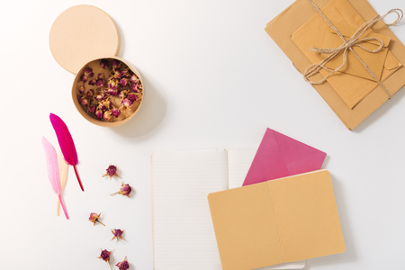 poems: Dried roses. Top view of a round paper box with dried roses lying on the desk near pink feathers and surrounded by envelopes Stock Photo