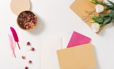 poems: Beautiful and aesthetic. Round small paper box being filled with dried roses and standing on the white desk near envelopes