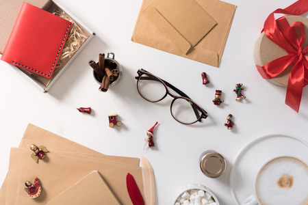 Winter holidays. Flat lay of small red toy figures being scattered on the white table