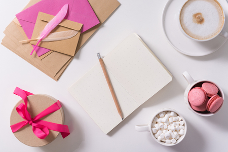 Confession love letter. Open notebook lying on the table and being surrounded by delicious sweets while being used for writing a confession love letter Stock Photo