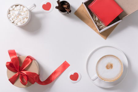 Day of love. Flat lay of different presents for the Valentines Day lying on the table decorated with paper hearts Stock Photo