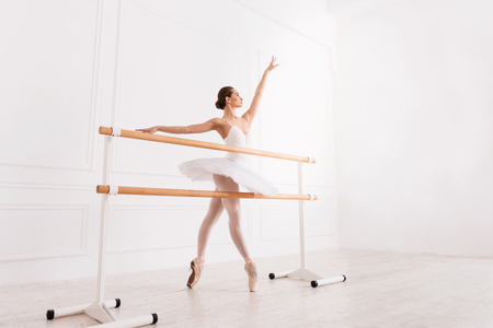 Here is your success. Tender young ballerina standing on tiptoes in semi position holding left arm upwards while touching the ballet bar