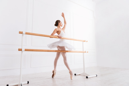 I will do my best. Young adorable woman in white tutu standing on tiptoes behind ballet bar keeping her left hand upwards looking sideways