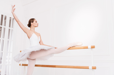 turnanzug: Elegance in the movements. Serious female wearing points and white leotard with tutu standing in semi position while stretching before performance