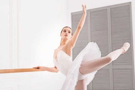 ballet bar: Look at me. Tender pretty woman wearing white dress with tutu holding left hand and leg upwards standing against white background