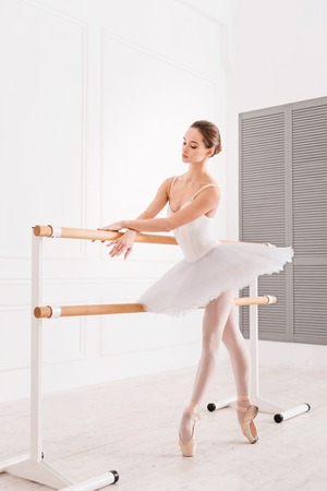 turnanzug: Elegant position. Full length picture of graceful female wearing leotard and white tutu looking at crossed hands while standing on tiptoes Lizenzfreie Bilder