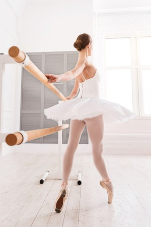Think a moment. Elegant female with bun on the head wearing points and white short dress while standing on tiptoes touching bar