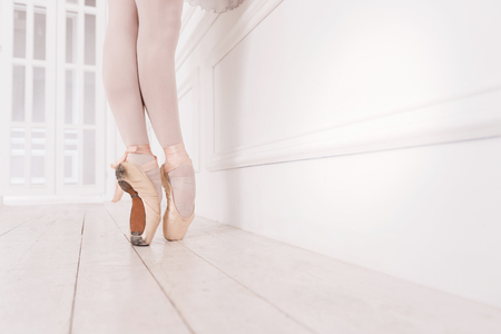 ballerina tights: Shoes for ballet. Professional ballerina wearing white tights and points standing on tiptoes while posing in dance studio Stock Photo