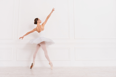It is my favorite. Pretty girl with bun on the head stretching her arms wearing white leotard with tutu posing on tiptoes