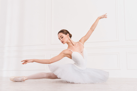 Follow my example. Serious young ballerina wearing white leotard with fluffy skirt looking down while stretching her leg on the floor Stock Photo