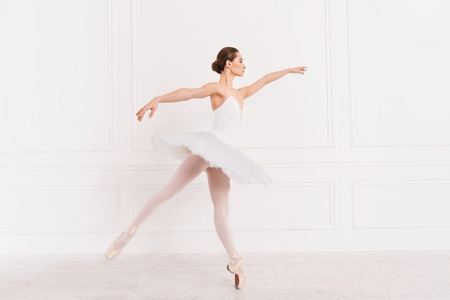 ballerina tights: Improve it. Graceful young woman wearing white leotard with tutu looking sideways keeping arms straight in the air