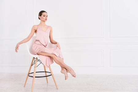 I am always serious. Supercilious young female wearing pink dress looking straight at camera keeping her legs straight while posing on the chair Stock Photo