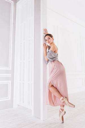 Be joyful. Elegant ballerina wearing beige points holding both hands on the wall while standing on tiptoes in ballet studio