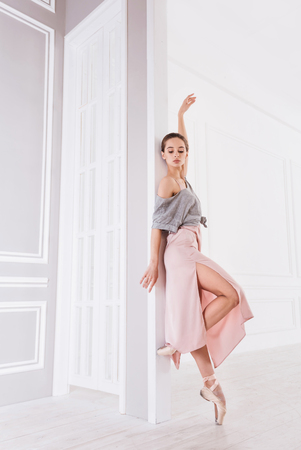 Stretch your body. Graceful ballet dancer wearing grey top over pink dress holding her shoulders bare staring head first Stock Photo