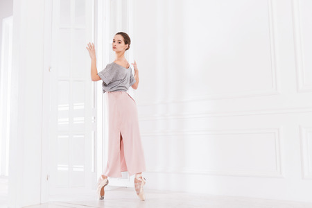 Strong toes. Graceful ballet dancer holding white doors with both hands looking at camera while standing on tiptoes Stock Photo