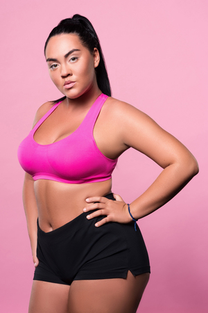 mulatto woman: Im so fancy. Portrait of nice mulatto woman standing and posing on isolated pink background.