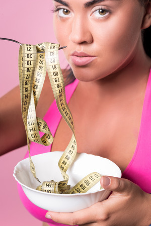 Don not overeat. Close up of pretty mulatto woman holding plate and fork at her mouth with rolled measuring tape on it. Stock Photo