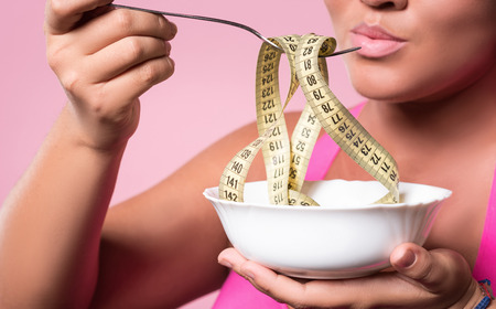 plumb: All superfluous centimeters. Close up portrait of plumb mulatto lady holding dish and fork with rolled measuring tape on it near her mouth. Stock Photo