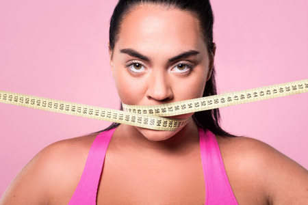 mouth close up: Stop eating. Close up portrait of chubby mulatto lady covering her mouth with body measuring tape against pink isolated background.