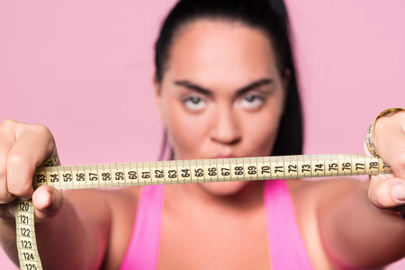 mulatto woman: Wanting be slim. Close up of body measuring tape held by chubby mulatto woman on isolated pink background.