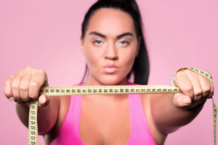 mulatto woman: My aim. Close up portrait of serious mulatto woman holding body measuring tape against isolated pink background.