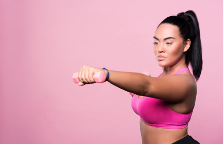 mulatto woman: Getting stronger. Pretty chubby mulatto woman doing boxing exercises with dumbbells while standing against isolated pink background.