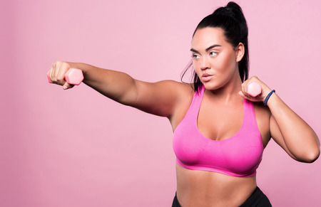 mulatto woman: Serious matter. Concentrated plump mulatto woman doing boxing exercises by using small dumbbells isolated on pink background.