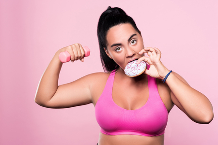 mulatto woman: Cheating on yourself. Funny plump mulatto woman doing dumbbell exercises and eating donut against pink isolated background.