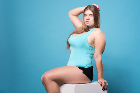 Being sexy. Attractive youthful chubby woman sexy posing while sitting against isolate blue background. Stock Photo