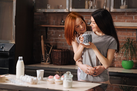 lesbian women: Nice day. Happy lesbian women standing in pajamas near the kitchen table looking to each other while embracing Stock Photo
