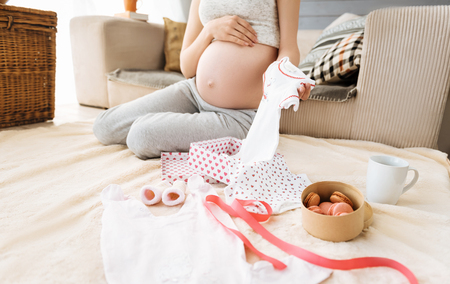 Close up of pregnant woman preparing baby clothes