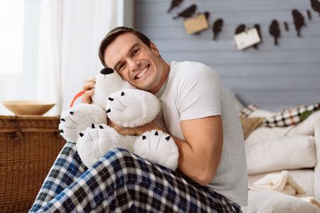 Happy joyful man hugging a stuffed animal